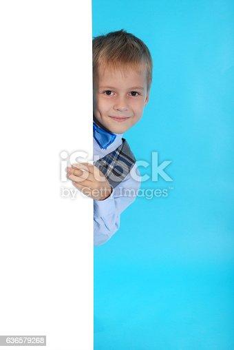 istock Smiling schoolboy posing behind a white billboard 636579268