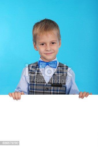 istock Smiling schoolboy posing behind a white billboard 636579292