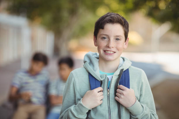 Smiling schoolboy standing with schoolbag in campus Portrait of smiling schoolboy standing with schoolbag in campus 12 13 years stock pictures, royalty-free photos & images