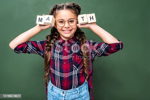 1016623732istockphoto smiling schoolchild holding wooden cubes with word math near blackboard 1016623622