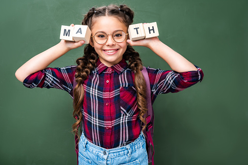 1016623732 istock photo smiling schoolchild holding wooden cubes with word math near blackboard 1016623622