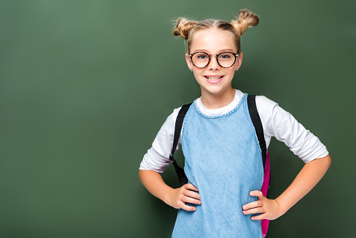 1016623732 istock photo smiling schoolchild in glasses posing near blackboard 1016623560