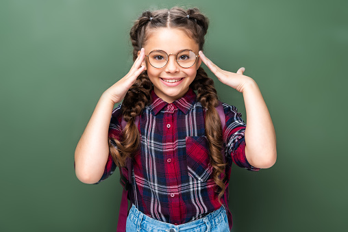 1016623732 istock photo smiling schoolchild touching head and looking at camera near blackboard 1016623620