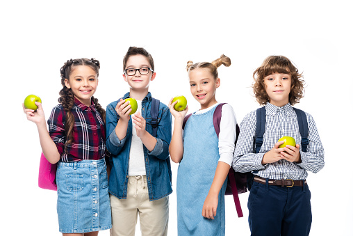 1016623732 istock photo smiling schoolchildren holding ripe apples isolated on white 1016623302