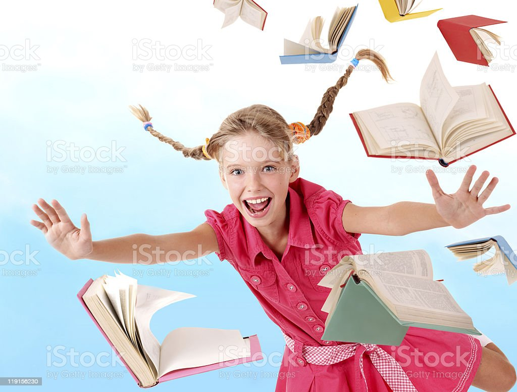 Smiling schoolgirl flying through a pile of books royalty-free stock photo