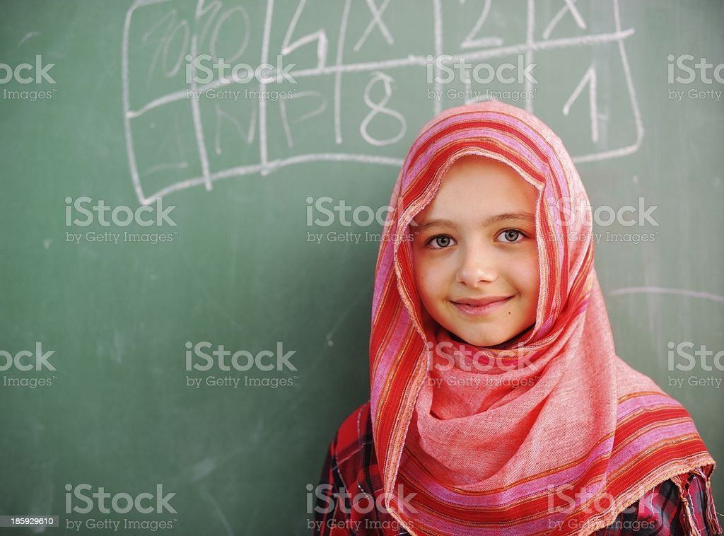 Smiling schoolgirl in front of a blackboard stock photo