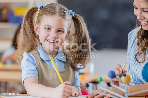 Adorable Caucasian young schoolgirl learns about the solar system. She is working on a worksheet. Her teacher is helping her.