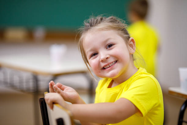 smiling schoolgirl looking at the camera sitting on chair in a classroom stock photo
