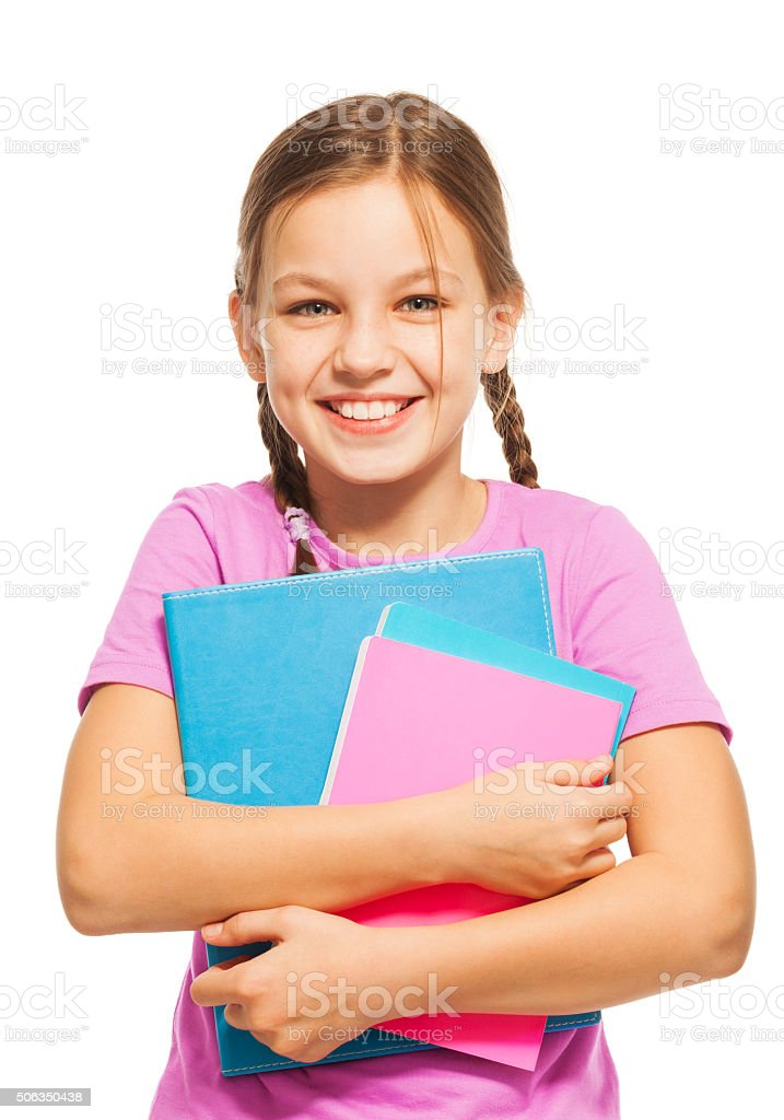 Smiling schoolgirl standing with her textbooks stock photo