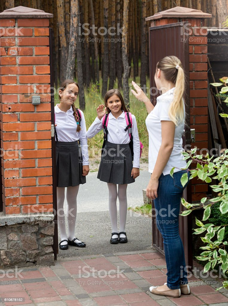 Smiling schoolgirls going to school and waving to their mother – Foto