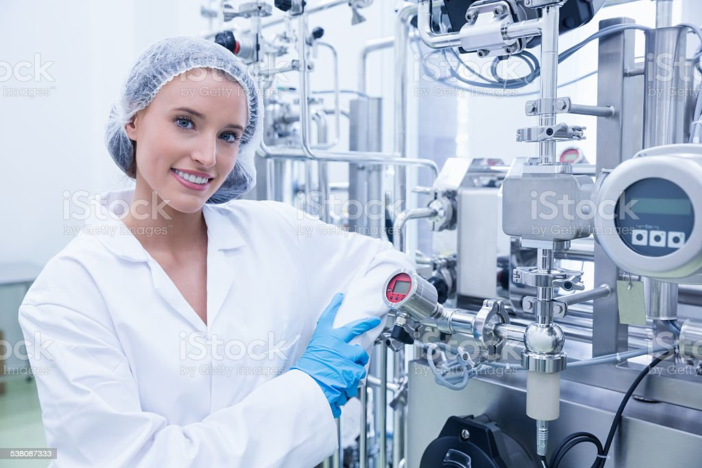 Smiling scientist leaning against gauge stock photo