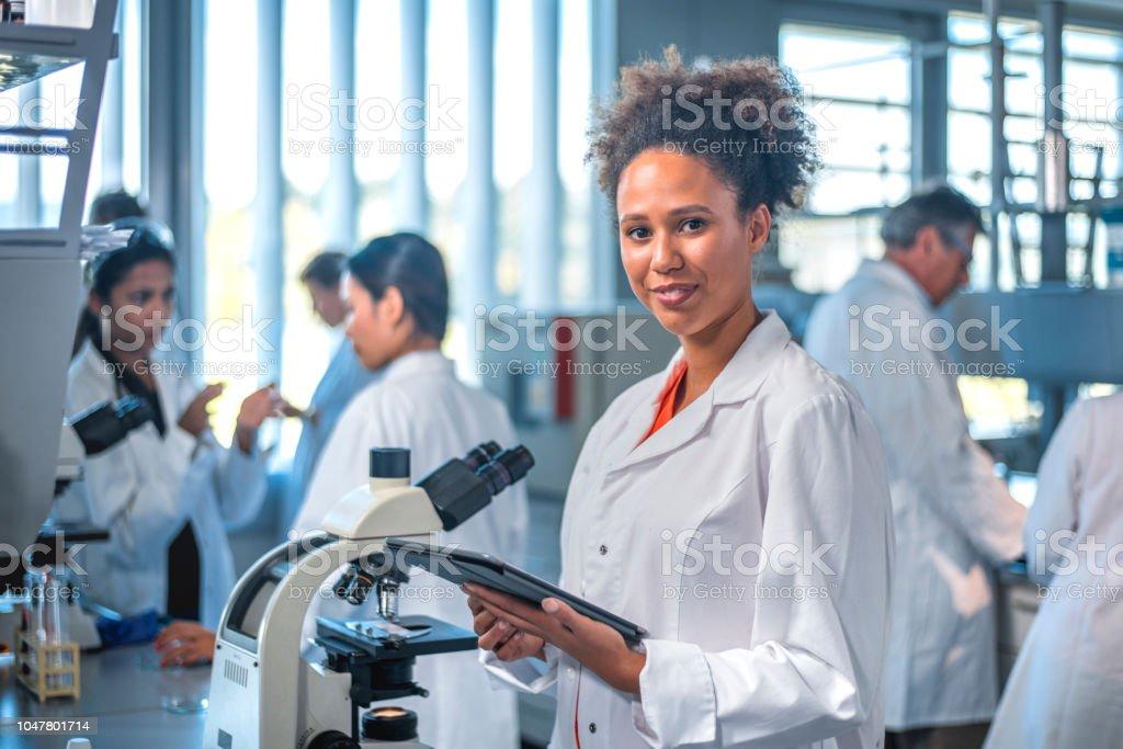 Lächelnde Wissenschaftler mit digital-Tablette im Labor – Foto