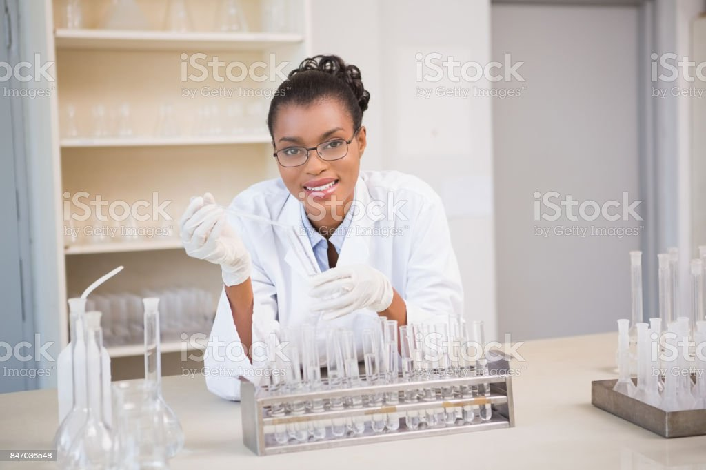 Smiling scientist working with pipette stock photo