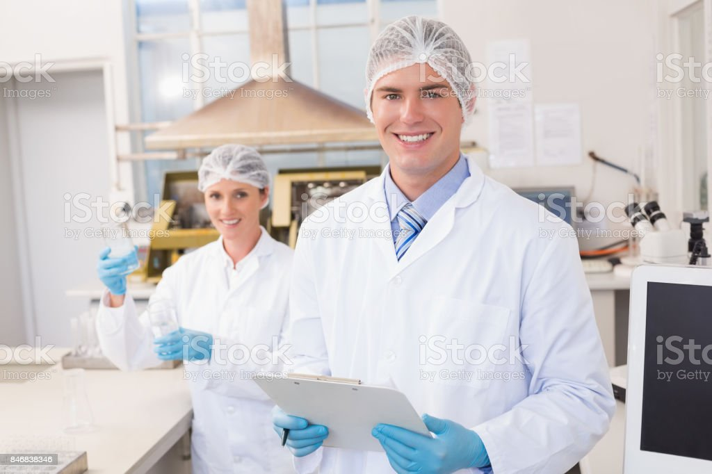 Smiling scientists looking at camera stock photo