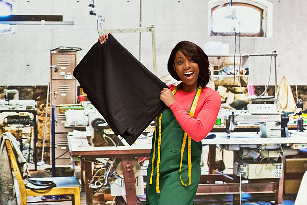 Smiling seamstress in textile industry stock photo