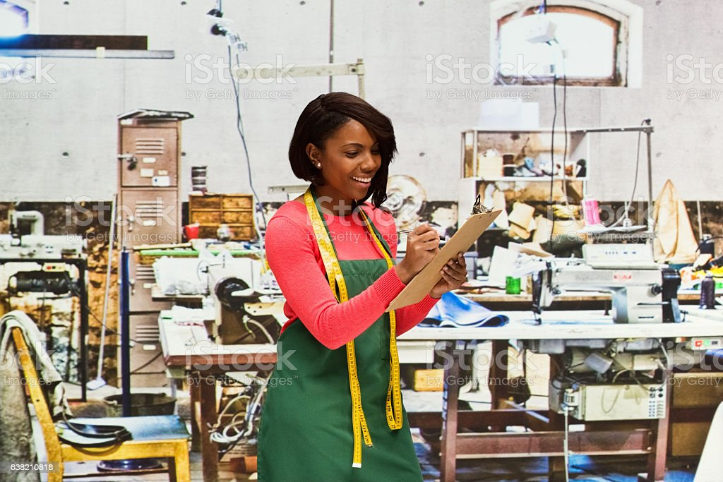 Smiling seamstress working in textile industry stock photo