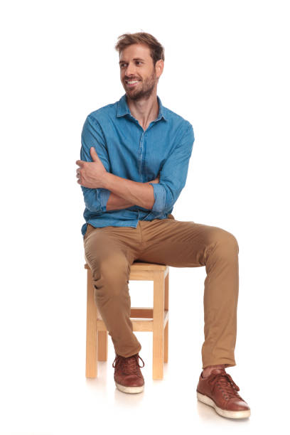 smiling seated young casual man looks to side smiling seated young casual man looks to side on white background sitting stock pictures, royalty-free photos & images