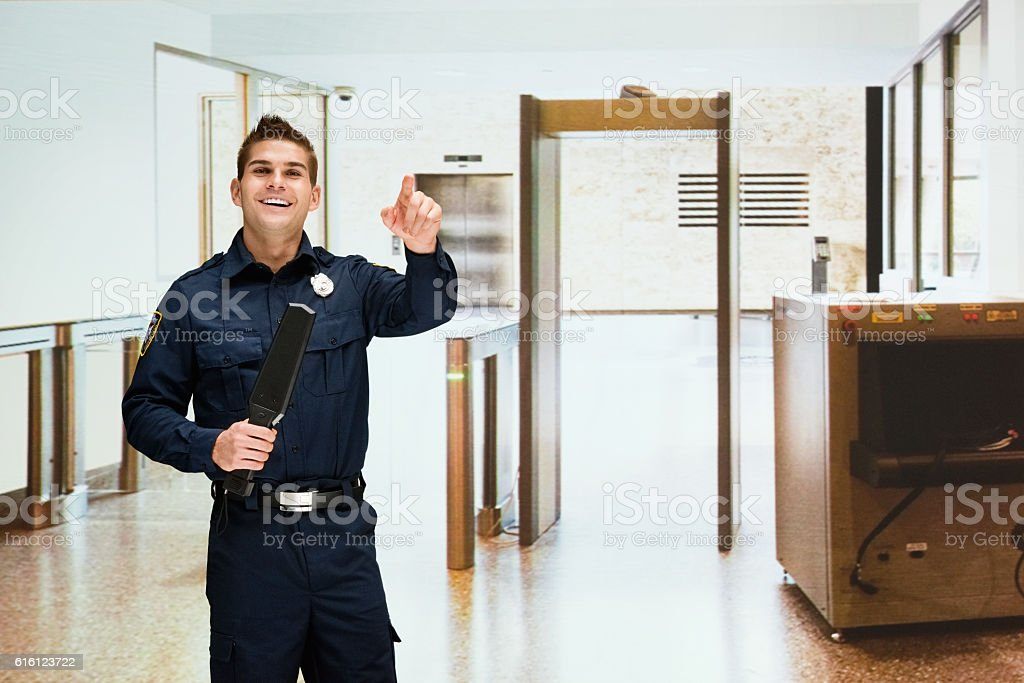 Smiling security guard standing indoors stock photo