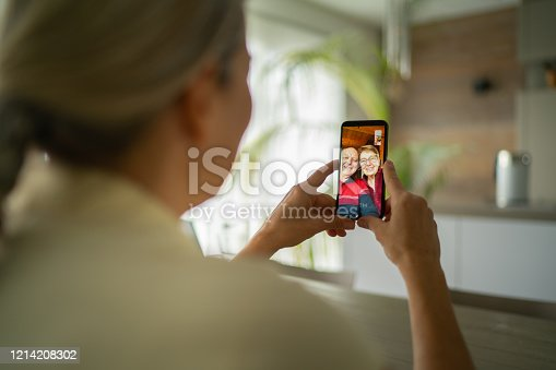 over the shoulder view mature adult woman talking with her smiling senior parents via mobile phone video telephony during corona quarantine in living room of house in times of social distancing to stay safe and healthy