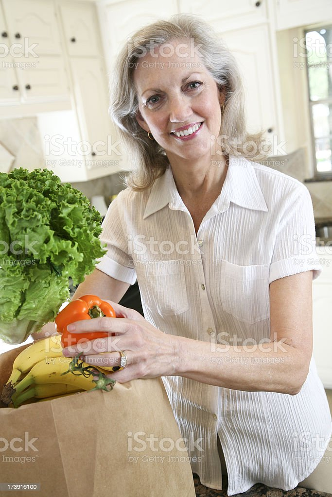 Smiling Senior Adult Unloading Groceries from the Bag royalty-free stock photo