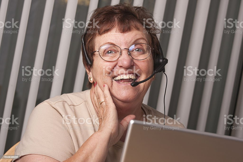 Smiling Senior Adult Woman with Telephone Headset and Monitor royalty-free stock photo