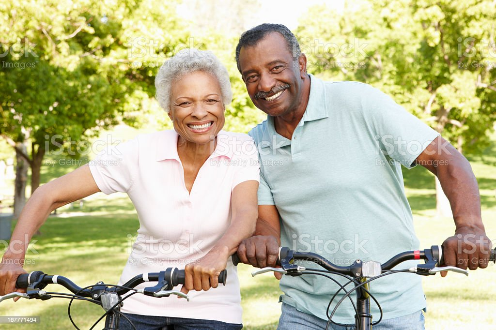 Smiling senior African American couple on bikes in the park stock photo