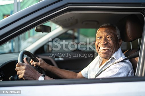 1051147634 istock photo Smiling senior afro man driving a car and looking at camera 1159586745