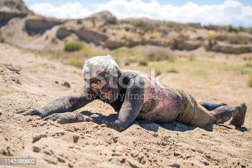istock Smiling senior at Issyk-Kul Salty Lake,  lying onbeach with mud over his body, Kyrgyzstan 1143685602