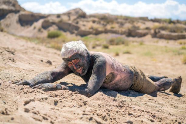 Lächelnde Seniorin am Issyk-Kul Salty See, am Strand liegend mit Schlamm über seinem Körper, Kirgisistan – Foto