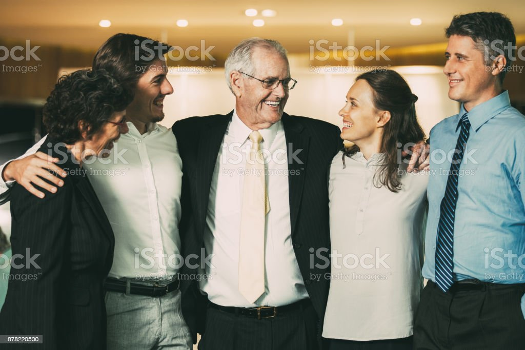 Smiling Senior Business Leader Embracing Coworkers stock photo
