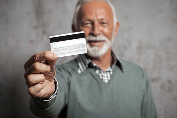 Lächelnder Senior Geschäftsmann hält Kreditkarte – Foto