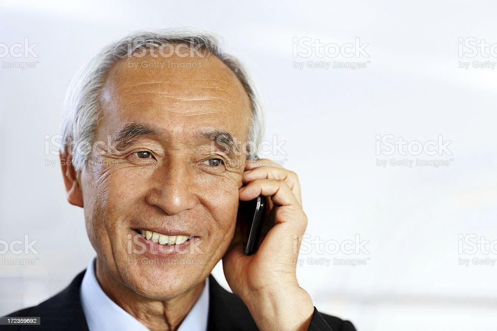 Smiling senior businessman talking on mobile phone royalty-free stock photo