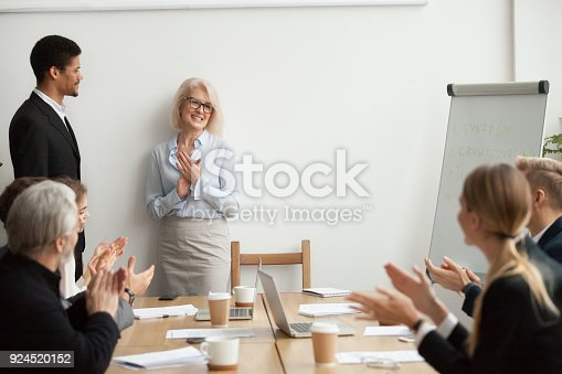 923041456 istock photo Smiling senior businesswoman boss and team clapping hands at meeting 924520152