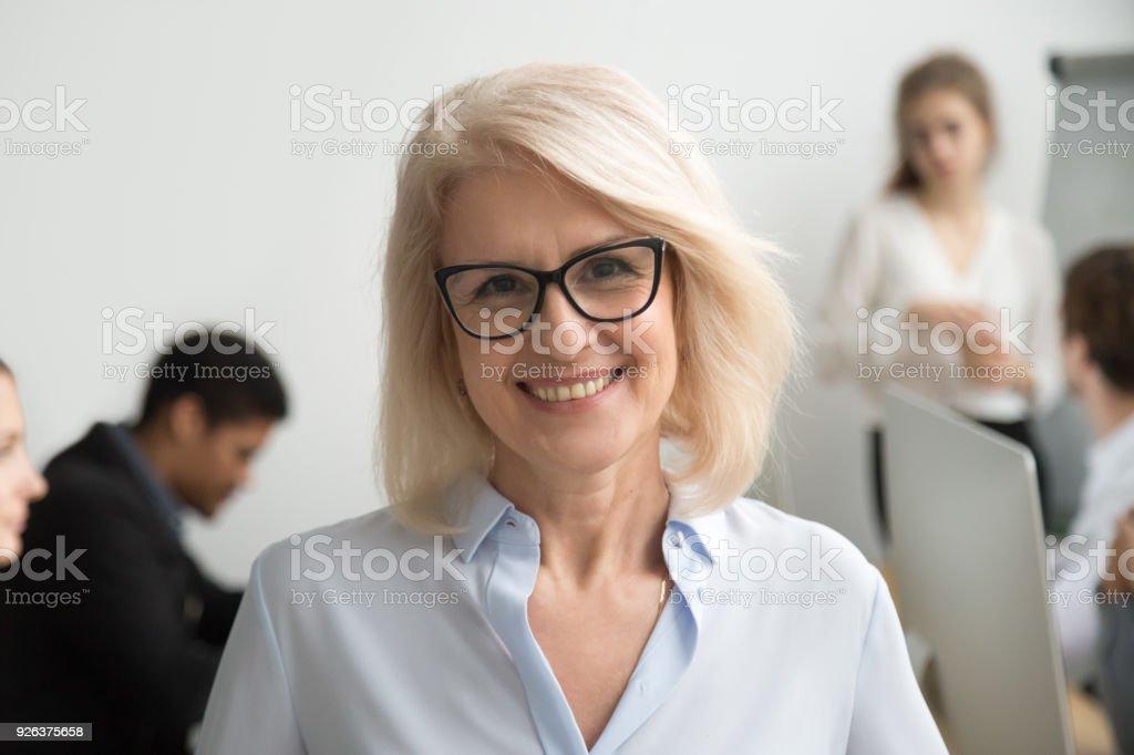 Sonriendo empresaria senior usa gafas retrato con empresarios en el fondo foto de stock libre de derechos