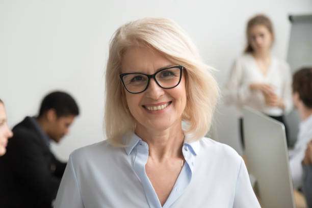 Smiling senior businesswoman wearing glasses portrait with businesspeople at background Portrait of smiling senior businesswoman wearing glasses with businesspeople at background, happy older team leader, female aged teacher professor or executive woman boss looking at camera, head shot director stock pictures, royalty-free photos & images
