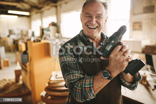 Smiling senior carpenter holding drill machine against workshop. Mature male worker smiling confidently to the camera holding drilling machine at his carpentry workshop.
