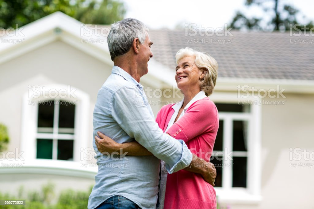 Smiling senior couple against house at yard foto stock royalty-free