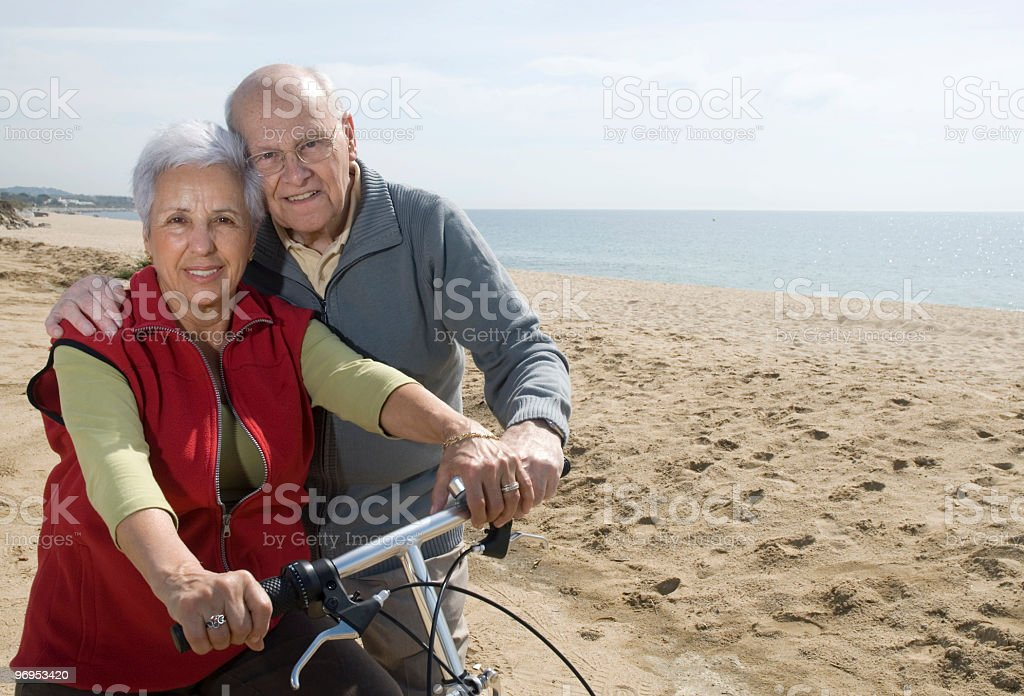 Smiling senior couple biking on the beach royalty-free stock photo
