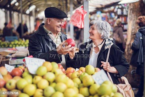 istock Smiling senior couple buying fruit together at farmer's market. 471079708