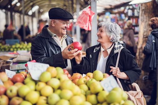 Smiling senior couple buying fruit together at farmer's market.