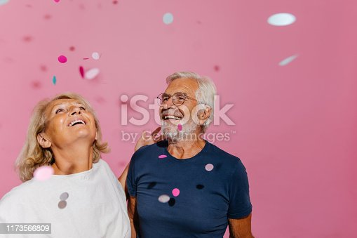 Portrait of a smiling senior couple celebrates their anniversary by throwing confetti up in the air