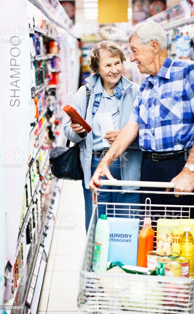 Smiling senior couple choosing toiletries in supermarket stock photo