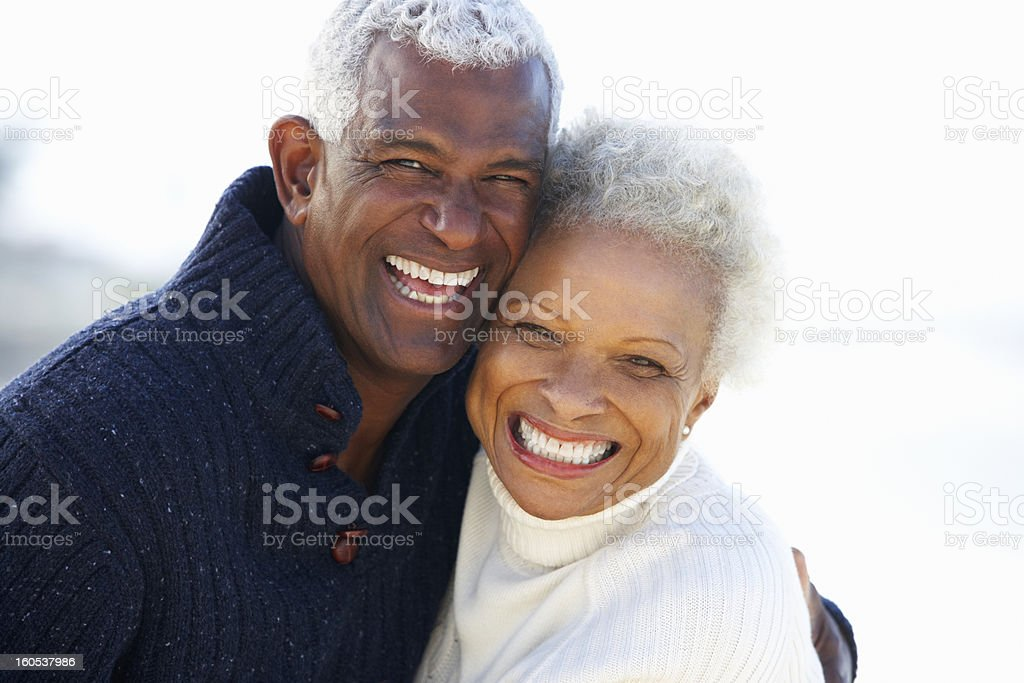 Romantic Senior Couple Hugging On Beach Smiling To Camera