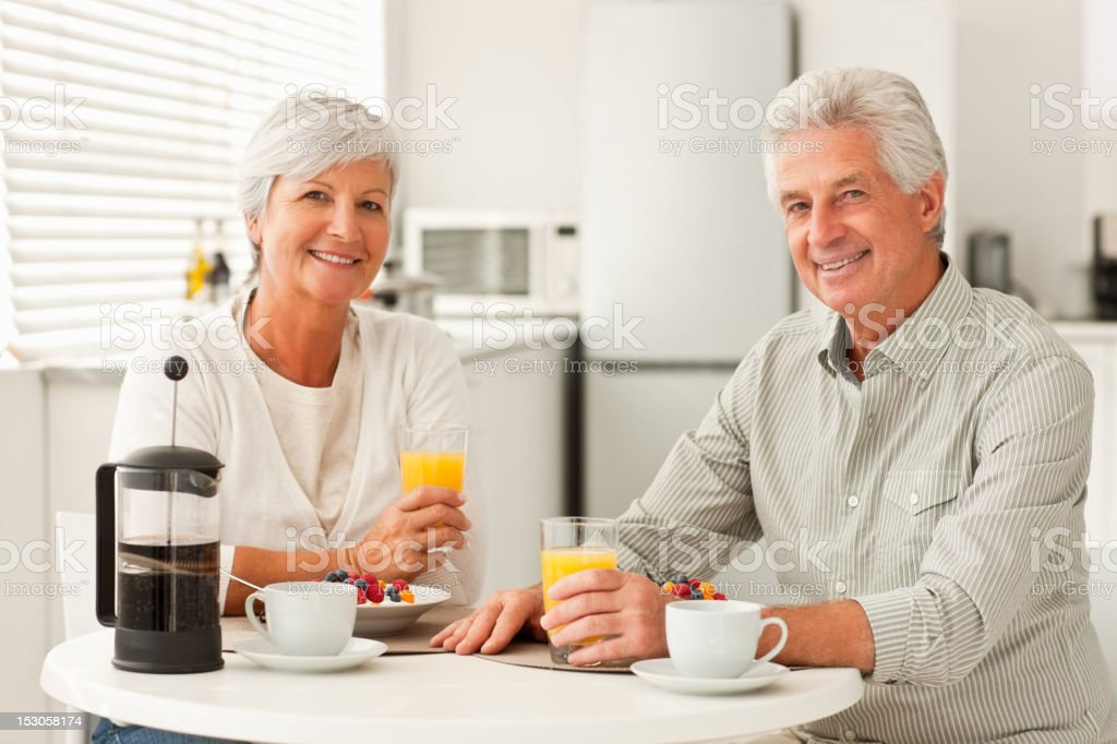Smiling senior couple having breakfast at home royalty-free stock photo