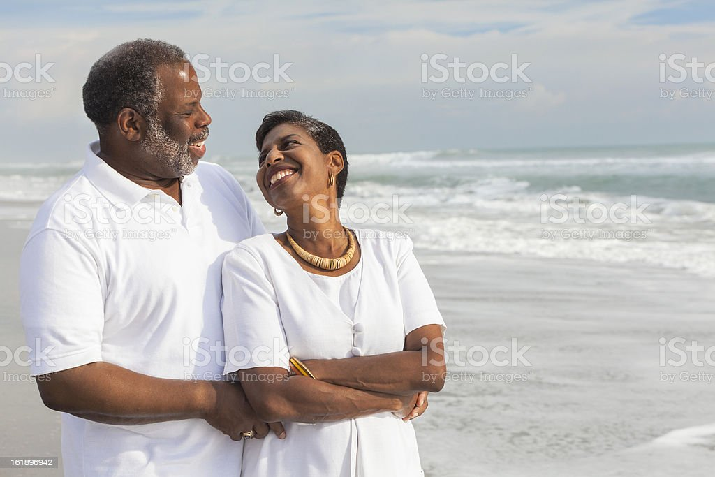 Smiling senior couple hold each other on a beach stock photo