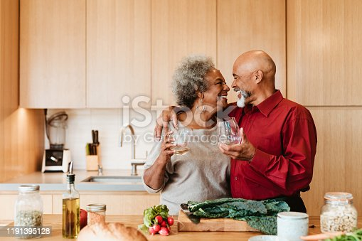 Happy man and woman looking at each other at kitchen island. Senior couple is holding alcoholic drink in kitchen. They are standing with arm around.