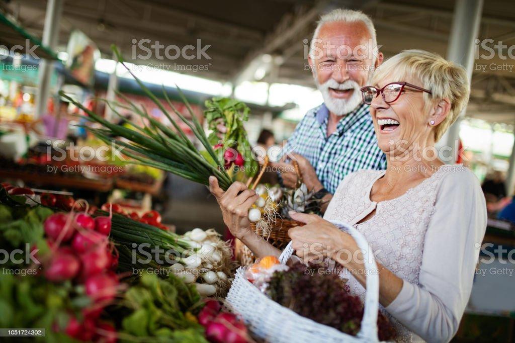 Lachende senior paar houden mand met fruit op de markt - Royalty-free Aanraken Stockfoto