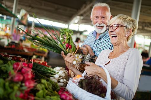 Lachende Senior Paar Houden Mand Met Fruit Op De Markt Stockfoto en meer beelden van Aanraken