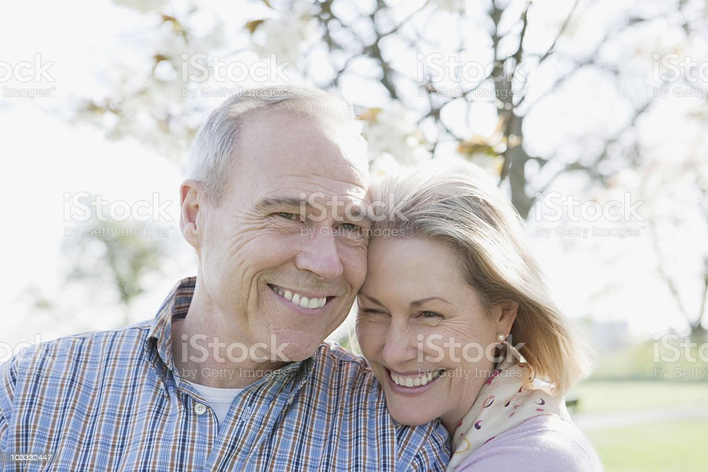 Smiling senior couple hugging in park royalty-free stock photo