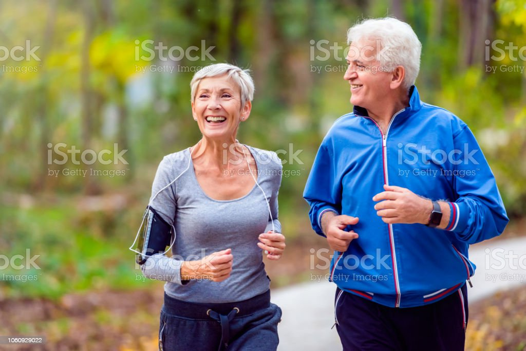 Smiling senior couple jogging in the park royalty-free stock photo